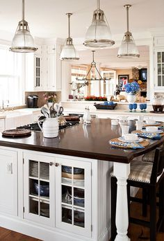 Crisp white kitchen in a summer home on Nantucket. Glass shelving on the bottom of the island and light fixtures reminiscent of ship lights add vintage charm - as seen in Traditional Home®