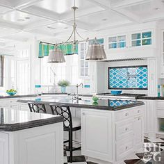 A bold pattern behind the range makes a striking statement in this all-white kitchen. The high-gloss finish of the backsplash tiles reflects light streaming in from the kitchen's many windows. The bold turquoise color echoes hues found throughout the rest of the house and recalls the views of the ocean through the windows.