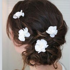Soft curls in low side bun bridal hairstyle. Another gorgeous look from our affiliates at Jewel Hair Design featuring our Kendra set of five silk flower hair pins. Perfect for a romantic wedding hairdo.