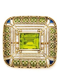 18 Karat Gold, Peridot and Plique-à-Jour Enamel Brooch, Tiffany & Co., Designed by Louis Comfort Tiffany. Centred by an emerald-cut peridot, within openwork frames composed of ropetwist and scrollwork motifs, applied at the borders with yellow-green and blue plique-à-jour enamel, signed Tiffany & Co.; circa 1910. #LouisComfort #Tiffany #ArtsCrafts #brooch
