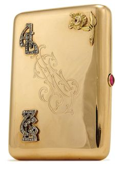 """A RUSSIAN GOLD AND GEM SET CIGARETTE CASE St. Petersburg 1899-1908. The polished body with hinged lid engraved with monogram, an applied two-colored gold rose charm and applied monograms embellished with diamonds. Verso with applied nickname """"Sema"""", garnished with diamonds and sapphire and with red cabochon thumbpiece. The interior engraved with a dedicatory inscription dated 1904. Hallmarked St. Petersburg 1899-1908, Cyrillic maker's mark of Andre Stepanovich Bragin,"""