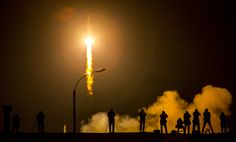 Fiery nighttime launch of Soyuz rocket at center left with media photographers in silhouette at right