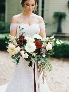 Rustic overflowing bold chrysanthemum, succulent and rose wedding bouquet: http://www.stylemepretty.com/2016/12/21/red-greenery-rustic-wedding/ Photography: A. Thomas - http://athomasphotography.com/#welcome-1