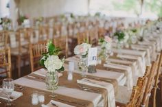 Simple & rustic. Burlap runners, lots of small floral arrangements in mason jars and a sprig of lavender at each place setting.