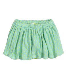 BABY EXCLUSIVE/CONSCIOUS. Een rok van een dubbele laag geweven biologisch katoen met elastiek in de taille. De rok heeft een vastgestikt onderbroekje van katoenen popeline met elastiek rond de beenopeningen.