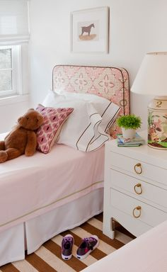 Cute casual rug between twin beds laid over larger rug and upholstered headboards in fun fabric