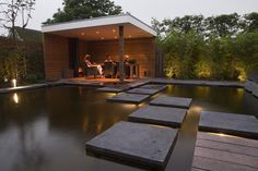 contemporary pergola with wood burning stove, garden filled by a large pond with modern stepping stones - Hoveniersbedrijf Jan Abrahams BV