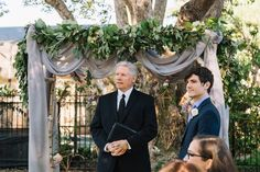 outdoor wedding arbor of birch is dressed with pale grey draping and 8 feet of lush salal/seeded eucalyptus & olive garland, and assorted humble lanterns.