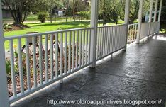 Stamped concrete porch floor with white porch railings
