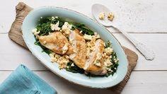Ein Teller mit überbackenem Hähnchenbrustfilet, Spinat und Fetakäse steht auf dem Tisch.