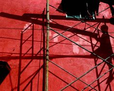 Shadow Of Worker On Red Wall