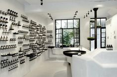 Designed by Ciguë, Aesop's new boutique in the Marais is a minimalist space featuring white concrete walls embedded with rows of metal saucers (repurposed plumbing pipe caps) that hold products in orderly rows. As in all Aesop stores, the space is part laboratory, part art installation.