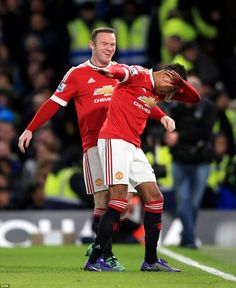 The 23-year-old midfielder celebrates with captain Wayne Rooney after firing Manchester Un...