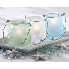 "Sea Glass Luminary  Each luminary measures 3.5"" tall, 3.25"" in diameter and arrives in an assortment of three colors including ocean blue, sea-foam white and tropic-sea green."