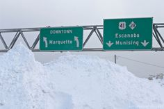 Highway signs for the cities of Marquette, Munising and Escanaba in the Upper Peninsula of Michigan in winter with snow piles. Marquette Michigan, Lake Michigan, Northern Michigan, Michigan Travel, Upper Peninsula, Mackinac Island, Great Lakes, Beautiful Landscapes, Landscaping