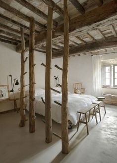 Trees as room divider in rustic Italian bedroom. Could leave as is, decorate with lights, hang dried herbs and flowers especially lavender, utilize as for hanging items-scarves, clothes, towels, drape muslin or even mosquito net if appropriate