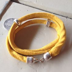 Handmade bracelet of yellow fabric with silver DQ clasp and charms