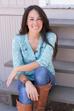 Host Joanna Gaines sits on the back steps of the Hendricks Family's renovated home, as seen on HGTV's Fixer Upper.