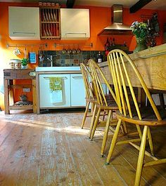 The yellow chairs and orange walls make this kitchen earthy and vibrant.