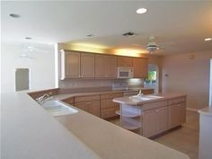 $949,000. L-shaped kitchen features island with additional sink.