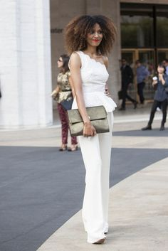 ESSENCE MAGAZINE | The Global Girl Press: Ndoema sports an all-white look: Valentino pants, vintage sequined peplum top and Onna Ehrlich Bianca gold metallic envelope clutch. With her signature big natural hair during New York Fashion Week.