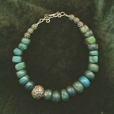 by Kathleen Botsford   Necklace comprising of lovely blue and green Hebron beads (beads made with salts from the Dead See and were produced in the mid 1800s) that have been combined with an antique Silver with inlaid turquoise bead.