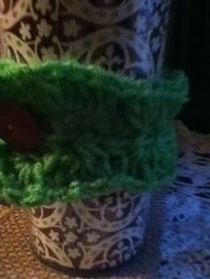 Green shell patter cup cozy with vintage adjustable button.