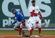 Dustin Pedroia #15 of the Boston Red Sox turns a double play as Ezequiel Carrera #3 of the Toronto Blue Jays reacts at second base in the eighth inning against he Toronto Blue Jays at Fenway Park on April 16, 2016 in Boston, Massachusetts.