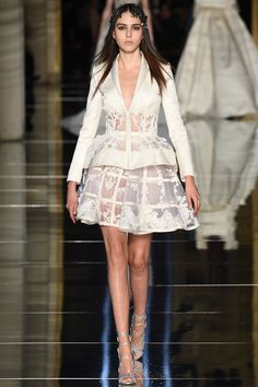 Zuhair Murad -The white jacket with deep V-neck and a sheer floral lace part at the waist, embroidered with lace appliques, paired with a cage skirt embroidered with floral guipure lace.Layering of the suit is quite effective.