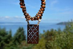 Wooden Mala Necklace with 108 beads; hand carved wooden focal point with brass inlays, wooden and bone beads strung on hand-knotted hemp.
