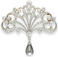 Antique diamond and pearl brooch by Tiffany and Co., circa 1895.  This brooch is designed as an openwork old European-cut diamond scrolled plaque, interspersed with collet-set diamonds. The diamond plaque suspends a drop-shaped pinkish brown pearl, measuring approximately 9.92 x 9.85 mm, with an old Euorpean-cut diamond cap, mounted in platinum-topped gold.  Via Diamonds in the Library.