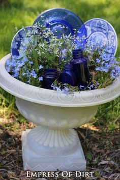 Garden junk tip: use dishes and bottles to fill in planters until the flowers are in full bloom.