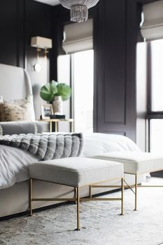 Well styled black and gray bedroom boasts square brass and linen stools placed on a gray Persian rug in front of a light gray wingback bed dressed in white bedding topped with a gold pillows and a gray fur throw lit by an Aerin Jacqueline Two-Tier Chandelier.