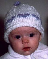 """Rolled Brim Baby Hat with a Topknot Size: Should fit a baby from monthsMaterials: 1 skein worsted wt. yarn, plus small amount of contrasting color for the hearts. If you do use a thicker yarn, you might need to make your """"s… The real thing! Baby Hat Knitting Patterns Free, Baby Hat Patterns, Baby Hats Knitting, Mittens Pattern, Crochet Baby Hats, Knit Or Crochet, Knit Patterns, Charity Knitting, Knit Hat With Brim"""
