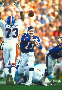 New York Giants quarterback Phil Simms tosses a pass around the  outstretched arms of Denver Broncos 45b936292