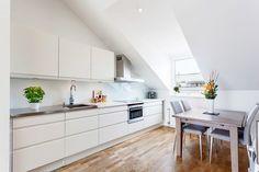matt weiße Küchenzeile, grifflose Fronten, Stahl Arbeitsplatte, Glas Spritzschutz