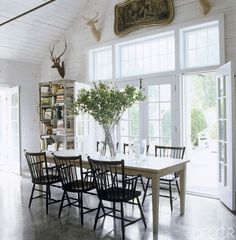 White-stained knotty-pine walls and polished con- crete floors form the backdrop for a table in the Millbrook, New York, dining room of jewelry designer Mish Tworkowski and his partner, Joseph Singer. The 1940s armchairs are by Stickley.