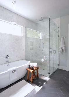 Gorgeous bathroom with full height marble subway tile backsplash, which continues into the shower, featuring a pendant above the freestanding tub with a wall mount tub filler beside a teak bathroom stool atop slate herringbone tiled floors leading to the corner walk in shower lined with gray marble grid tile floors.