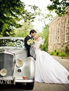 Kissing by a vintage Rolls Royce would make a lovely wedding photoshoot