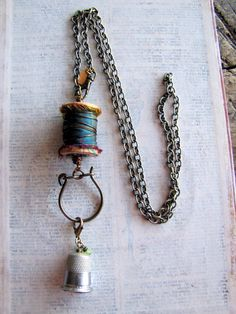 "Artist Amanda Davie, sewing charms necklace.  She re-purposed some popular sewing necessities, including a vintage thimble re-purposed into a charm. Necklace measures 28"", features a front swivel clasp."