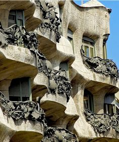 Casa Milà - Just look at his Casa Milà (aka La Pedrera): nothing about it looks assembled, or built. Instead it looks like Gaudí plopped it there as a huge mountain of slippery clay then dug his thumbs and fingers into it to make windows, doors, balconies, and even chimneys.