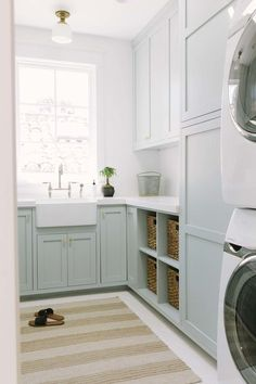 Beside a stacked white front loading washer and dryer, blue green shelves hold woven bins beneath a white quartz countertop fixed under blue green sha… – Laundry Room Mudroom Laundry Room, Laundry Room Layouts, Laundry Room Design, Laundry Bin, Living Room Designs, Living Room Decor, Green Shelves, Laundry Room Inspiration, Green Cabinets