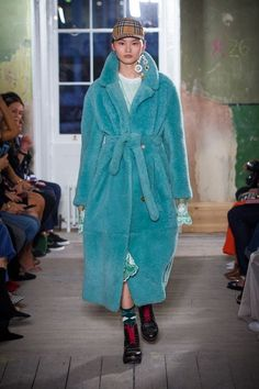 An oversized teddy-bear shearling coat styled over a green tulle dress with black clog boots and knitted socks. A Vintage check baseball cap completes the look.