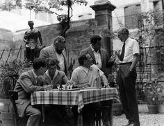 Lo scrittore Graham Greene, l'attore Trevor Howard, lo sceneggiatore Guy Elmes, l'attrice Alida Valli, il fotografo Enzo Serafin e lo scrittore Mario Soldati conversano attorno a un tavolo. Venezia, 1954