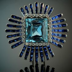 The Aquamarine Starburst Brooch by Verdura Paris, 1948 A French platinum brooch set with an emerald-cut aquamarine weighing approximately 30 carats. Framed with brilliant-cut diamonds and surrounded by a starburst set with calibre-cut sapphire sprays. The brooch was designed by Fulco di Verdura and produced by Verdura Paris in 1948. It was subsequently purchased by the Standard Oil heiress Millicent Rogers.