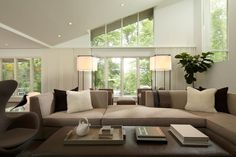 This modern, white living room has vaulted ceilings and neutral furniture that gives it a sleek and modern vibe.