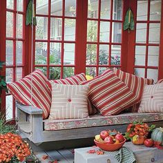 Bright Red Porch | Red is the defining color throughout this outdoor space. Using a single hue is an easy way to tie the look together. Extra pillows add color and comfort. | SouthernLiving.com