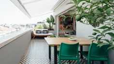 A long social space dotted with green elements forms one half of this apartment, located in a 1930s neighbourhood in Lisbon, Portugal.