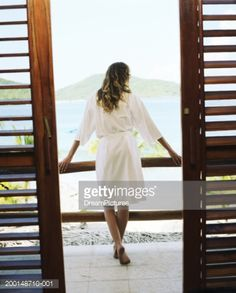 Stock Photo : Young woman in bathrobe looking out of hotel balcony, rear view