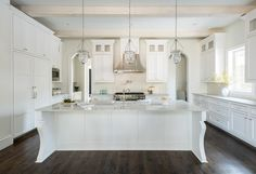 Spacious white kitchen is illuminated by three bell jar lanterns hung above a white island accented with curved legs and a white quartzite countertop fitted with a sink and a vintage style hook and spout faucet.